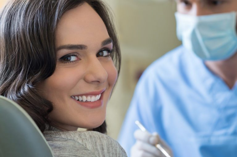 woman in dental seat smiling, with dentist wearing mask in the background
